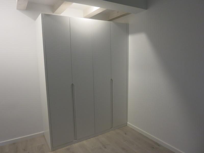 Armario con puertas abatibles y lateral visto.